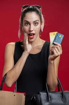 Shocked woman showing her credit cards