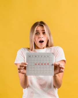 Shocked woman showing her period calendar front view