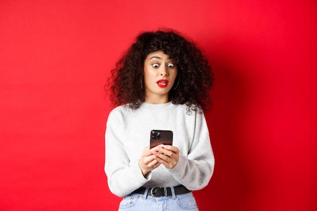 Donna scioccata fissa lo schermo dello smartphone con gli occhi aperti, legge uno strano messaggio, in piedi su sfondo rosso.