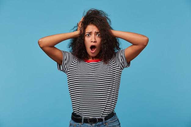 충격을받은 여성은 정면을 응시하고 입을 벌리고 머리를 긁고 놀랍게 보입니다.