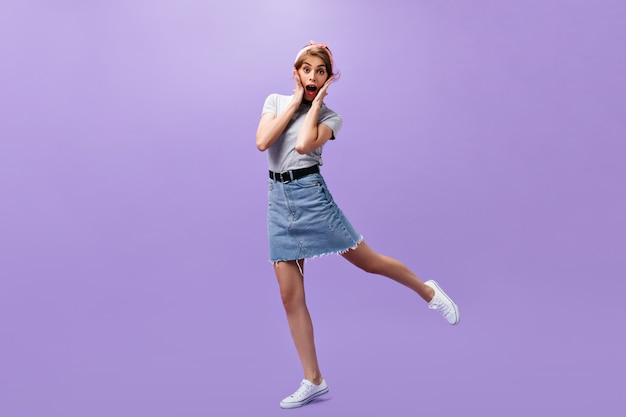 Shocked woman in stylish outfit jumps on purple background. surprised modern lady in grey t-shirt and denim short skirt posing.