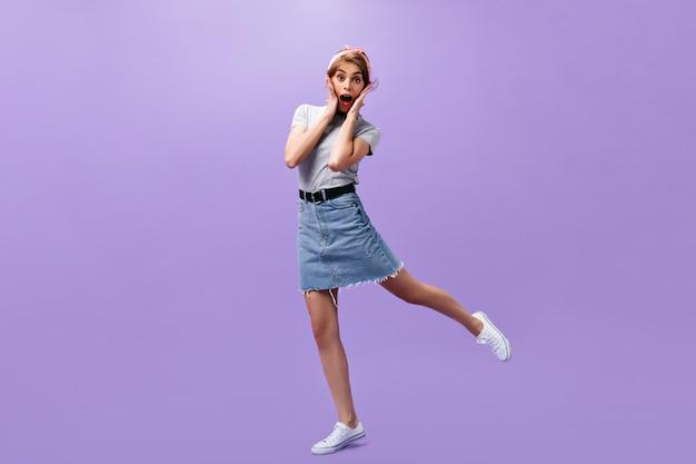 Donna scioccata in abito elegante salta su sfondo viola. signora moderna sorpresa in t-shirt grigia e gonna corta in denim in posa.