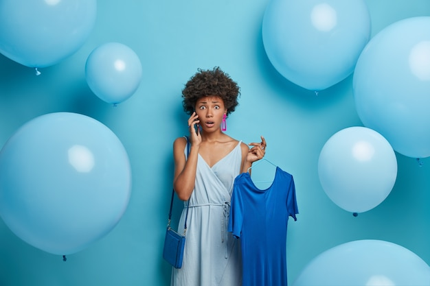 Shocked woman talks with friend via cellular, finds out exciting news, likes blue color, holds dress on hanger, dresses for going out, stands indoor with helium balloons, has perplexed worried look