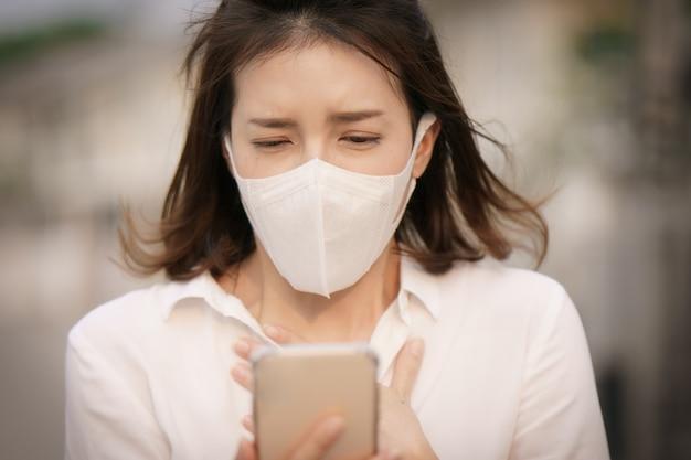 Шокированная женщина, носящая защитную маску от вируса короны (covid-19), пользуется смартфоном, переживая из-за новостей о вирусе короны.