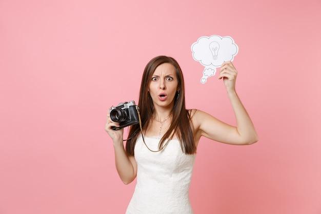 Una donna scioccata in abito bianco tiene in mano una macchina fotografica vintage retrò, dice nuvoletta nuvola con una lampadina che sceglie il personale, fotografo
