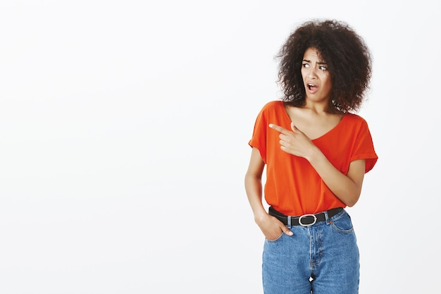 Shocked woman with afro hairstyle posing in the studio