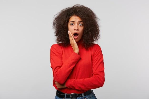 La donna scioccata con l'acconciatura afro fissa davanti, con la mano aperta della bocca vicino alla guancia, sembra sorprendentemente