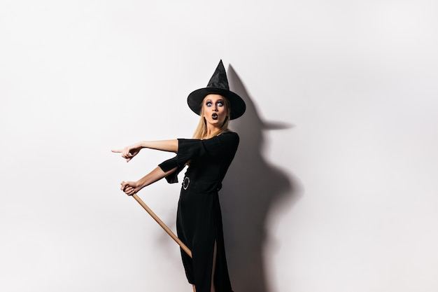 카니발에서 포즈를 취하는 검은 입술으로 충격 된 여자. 할로윈을 축 하하는 마녀 의상에서 감정적 인 소녀입니다.