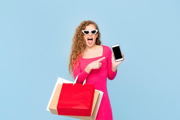 Shocked woman with colorful shopping bags yelling and pointing to mobile phone isolated