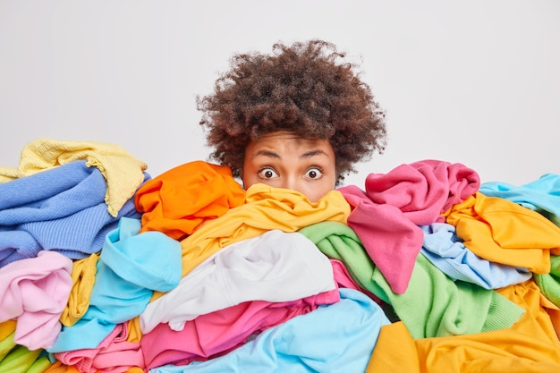 Shocked woman with curly afro hair stares bugged eyes drowned in huge pile of colorful clothing cleans out closet selects clothes for donation or recycling white