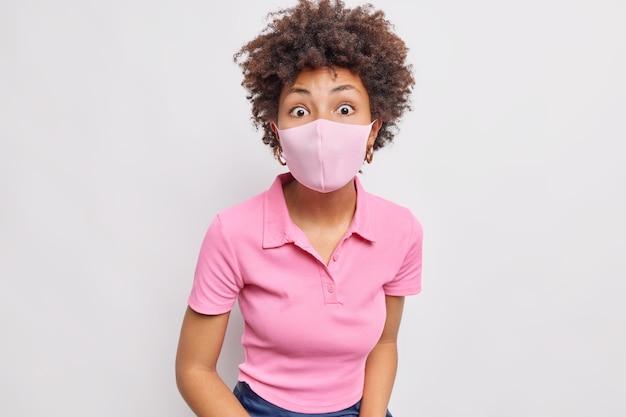 곱슬머리 아프로 머리를 한 충격을 받은 여성은 일회용 안면 마스크를 착용하고 흰 벽에 격리된 코로나바이러스 전염병 동안 자신을 보호하는 놀라운 소식에 반응합니다