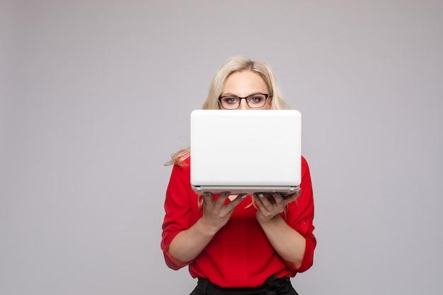 コンピューターを維持する口を開けてショックを受けた女性孤立した背景に驚いた若い実業家