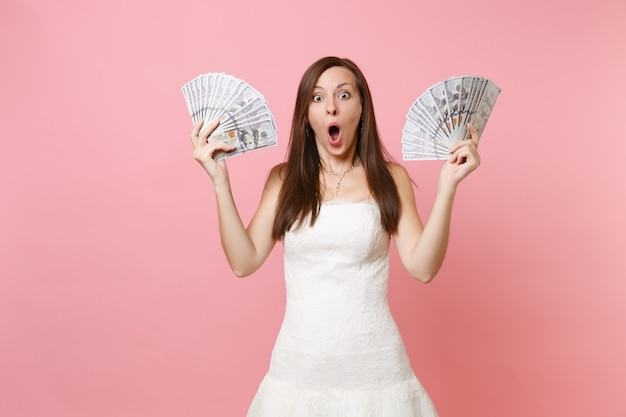 Shocked woman with opened mouth in white dress holding bundle lots of dollars, cash money