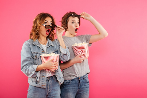 Shocked women friends eating popcorn watch film.