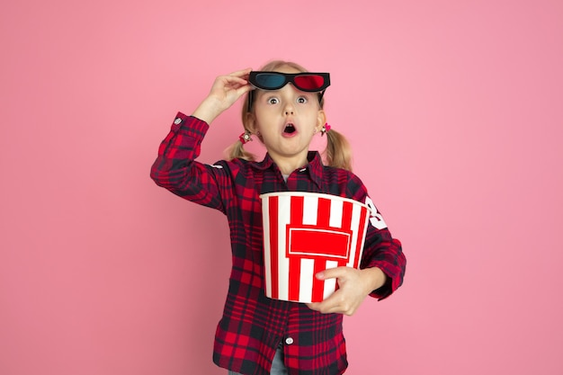 Shocked, wondered young girl with popcorn and 3d glasses on pink wall