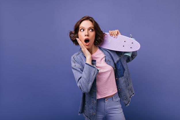 デニムの服を着てポーズをとるショックを受けた素晴らしい若い女性。スケートボードで立っている恍惚とした女の子の肖像画。