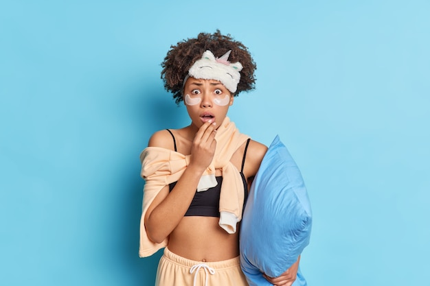 곱슬 머리를 가진 충격 걱정 아름다운 아프리카 계 미국인 여자는 파란색 벽 위에 절연 베개를 보유하고 편안한 파자마를 입고 무언가를 두려워하고 놀란 쳐다보고