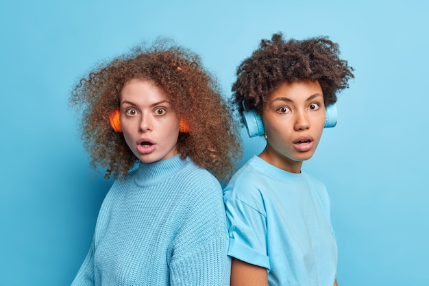 Shocked worried culy haired female best friends stare speechless have startled face expressions stand back to each other wear stereo headphones on ears dressed casually isolated over blue wall