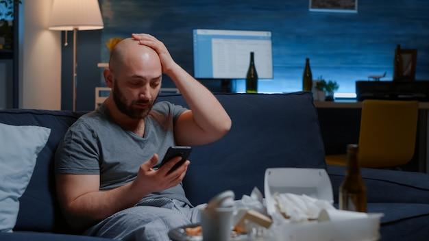 Шокированный встревоженный мужчина предупреждением о неоплаченных банковских счетах, полученных на смартфон, кладет хан ...