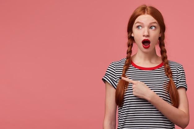 Шокированная взволнованная девочка-подросток с двумя рыжими косами, красная помада, открытая пасть, в панике, указывая пальцем, привлекает ваше внимание, чтобы скопировать пространство, встревоженная лицом огромной проблемы, озадаченной розовой стеной