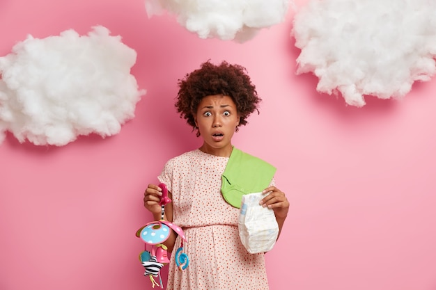 Shocked worried young afro american woman being pregnant holds diaper and mobile toy for baby wears dress puzzled as packs stuff for maternity hospital for first time. anticipation birth concept