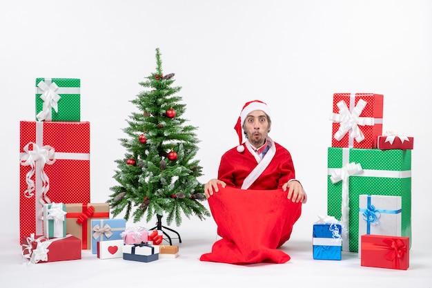 Scioccato giovane adulto vestito da babbo natale con doni e albero di natale decorato seduto per terra alla ricerca di qualcosa su sfondo bianco
