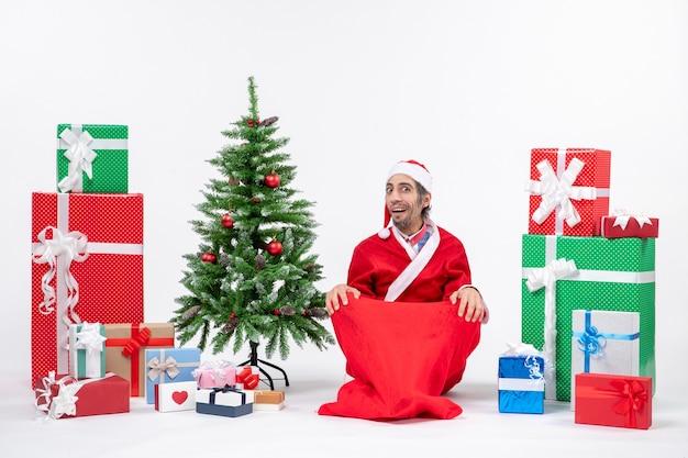 Scioccato giovane adulto vestito da babbo natale con doni e albero di natale decorato seduto per terra su sfondo bianco