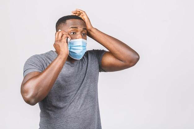 Шокирован молодой афро-американский мужчина в стерильной маске. с помощью телефона.