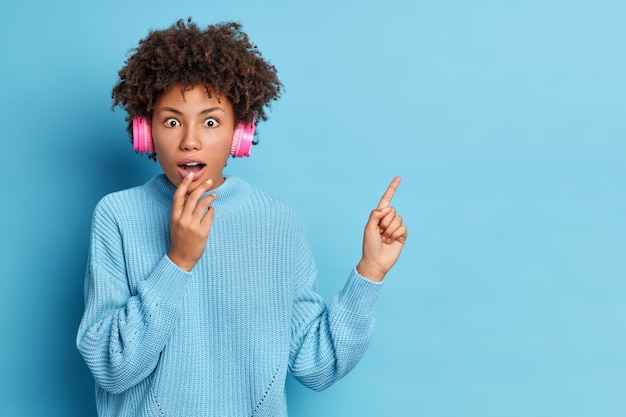 Shocked young african american woman looks with wonder keeps mouth opened wears strereo headphones listens favorite music indicates at copy space wears knitted sweater