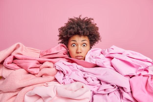ショックを受けた若いアフリカ系アメリカ人女性がカメラに唖然とした洗濯物の凝視の山に頭を突き刺す