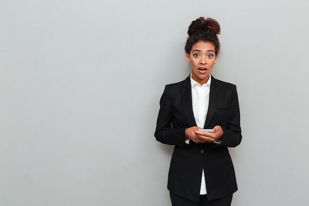 Shocked young african business woman standing over grey wall