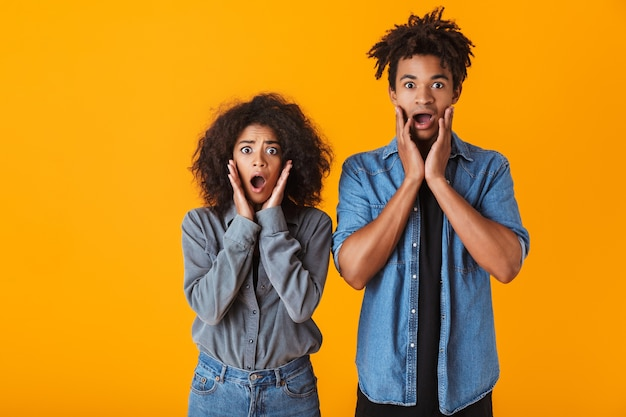 Shocked young african couple standing isolated, screaming