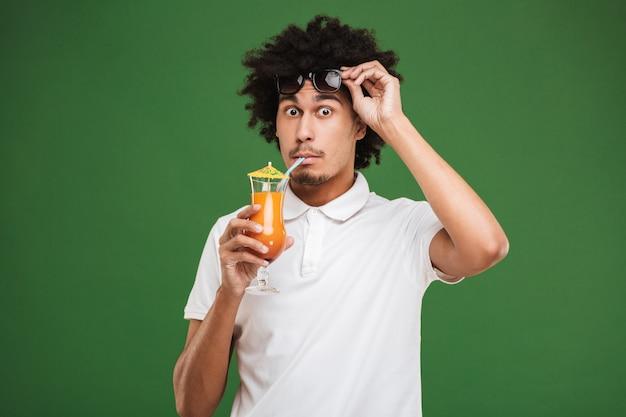 カクテルを飲んでショックを受けた若いアフリカ巻き毛の男。