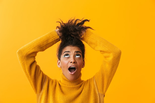 Shocked young african woman wearing sweater standing isolated