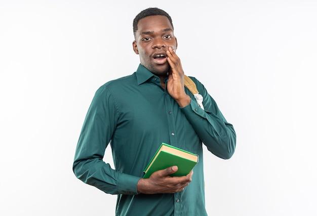 本を保持し、コピースペースで白い壁に隔離された彼の顔に手を置くバックパックでショックを受けた若いアフリカ系アメリカ人の学生