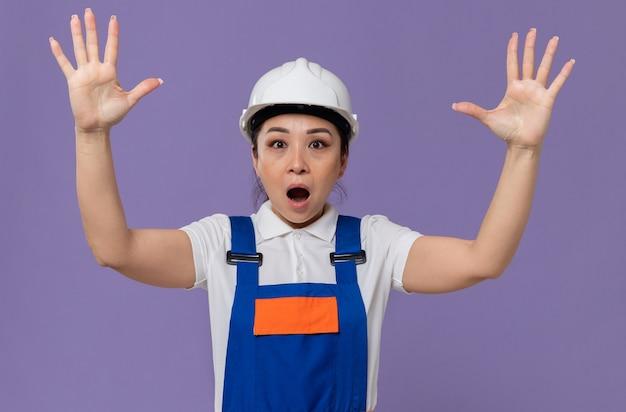 上げられた手で立っている白い安全ヘルメットを持つショックを受けた若いアジアのビルダーの女性