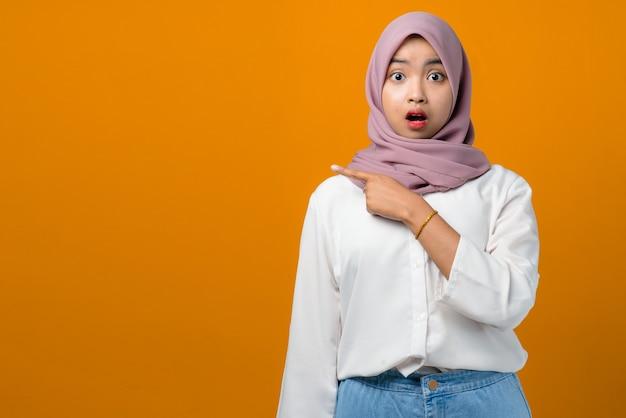 Шокированная молодая азиатская женщина, указывая в сторону на желтом