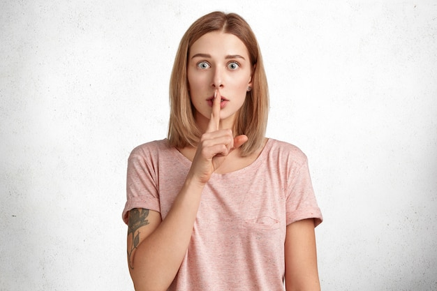 Shocked young attractive female keeps fore finger on mouth as demonstrates silence sign, looks with unexpected