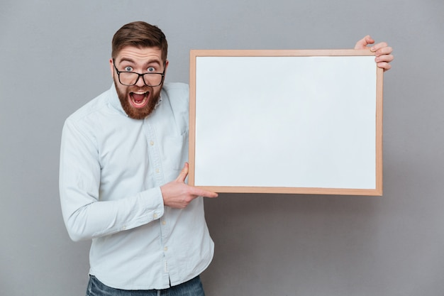 Shocked young bearded businessman holding blank board