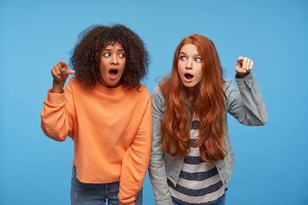 Shocked young beautiful women looking amazedly on each other with wide eyes and mouths opened, showing  with raised index fingers, posing over blue wall