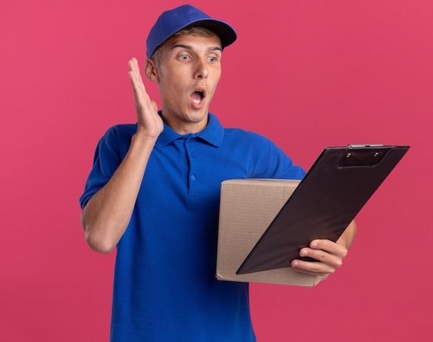 Il giovane ragazzo delle consegne biondo scioccato sta con la mano alzata e tiene una scatola di cartone guardando gli appunti isolati sulla parete rosa con spazio per le copie