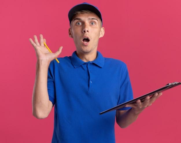 Il giovane ragazzo delle consegne biondo scioccato sta con la mano alzata e tiene la lavagna per appunti isolata sulla parete rosa con lo spazio della copia
