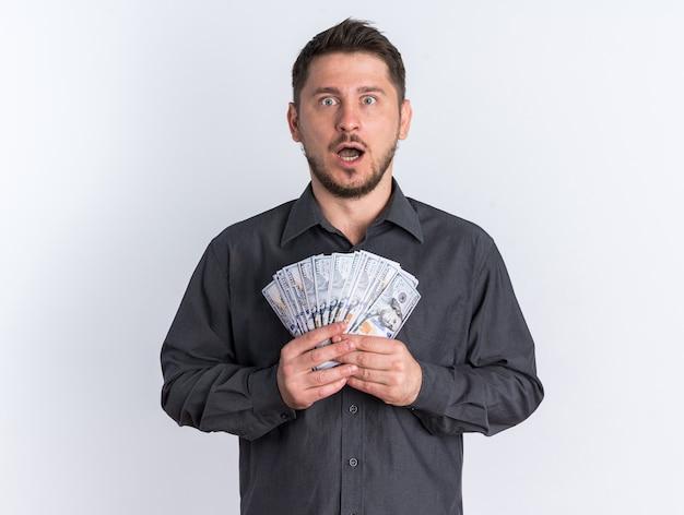 Шокированный молодой блондин красивый мужчина держит деньги с открытым ртом, глядя в камеру