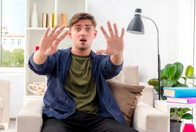 Шокированный молодой белокурый красавец сидит на кресле и жестикулирует пальцами в гостиной