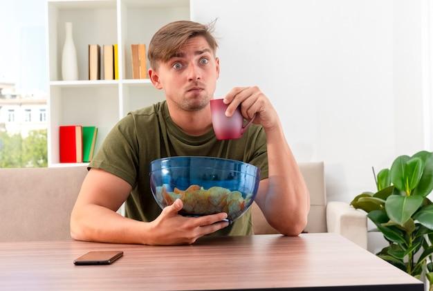 Scioccato giovane biondo bell'uomo si siede al tavolo con il telefono che tiene una ciotola di patatine e tazza all'interno del soggiorno