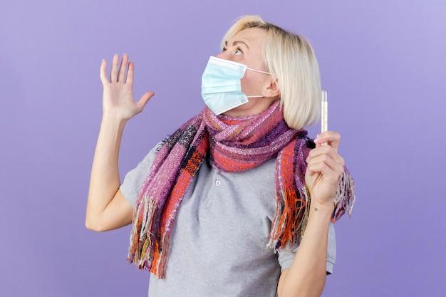 Scioccato giovane bionda malata donna slava che indossa sciarpa e maschera medica