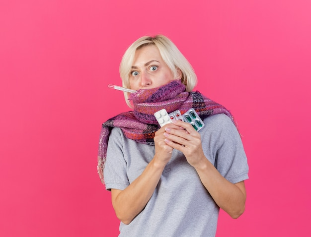 Sciarpa da portare della giovane donna slava malata bionda scioccata tiene confezioni di pillole mediche di misurazione