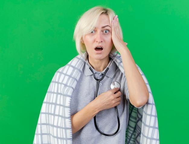 格子縞に包まれたショックを受けた若いブロンドの病気のスラブ女性は、頭に手を置き、コピースペースで緑の壁に隔離された聴診器を保持
