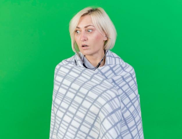 격자 무늬에 싸여 청진 기 충격 된 젊은 금발의 아픈 여자는 녹색 벽에 고립 된 측면에서 보인다