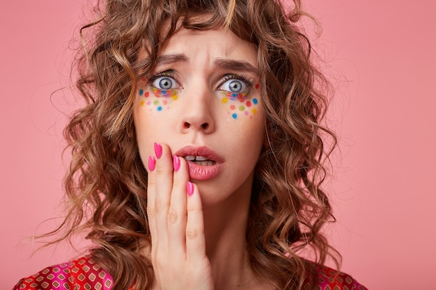 手のひらで彼女の頬を保持し、開いた目を開いて、色のパターンのトップでポーズをとって、お祝いの髪型を持つショックを受けた若い青い目のブルネットの女性